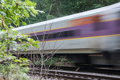 Boston commuter train flying by Walden Pond.