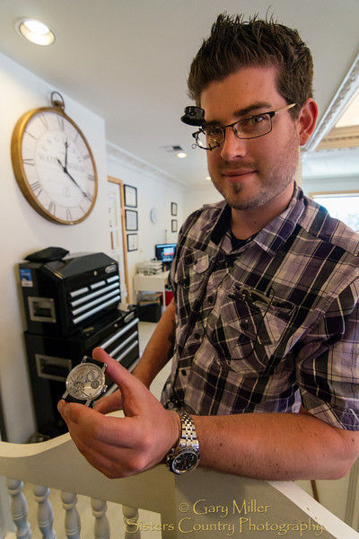 At Beacham's Clock Company in Sisters Oregon Keaton Myrick displays one of his custom watches that are true pieces of metallic art. Almost every single piece of this watch has been hand crafted down to screws that are so small it is impossible to see the threads with the naked eye. Image captured for the ADay.org project May 15, 2012 by Gary N. Miller - Sisters Country Photography