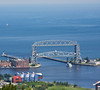 This is the iconic Lift Bridge at Duluth, MN. When large boats want in the harbor, the bottom of the bridge raises for entrance, and in the lower position it's an auto bridge to a long island. If one lives on the island it's best to leave for work a little early, I guess. The Great Lakes Aquarium is in the foreground. June, 2010.