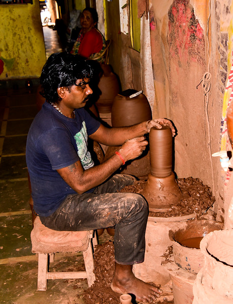 slum worker, making a clay pot in his home