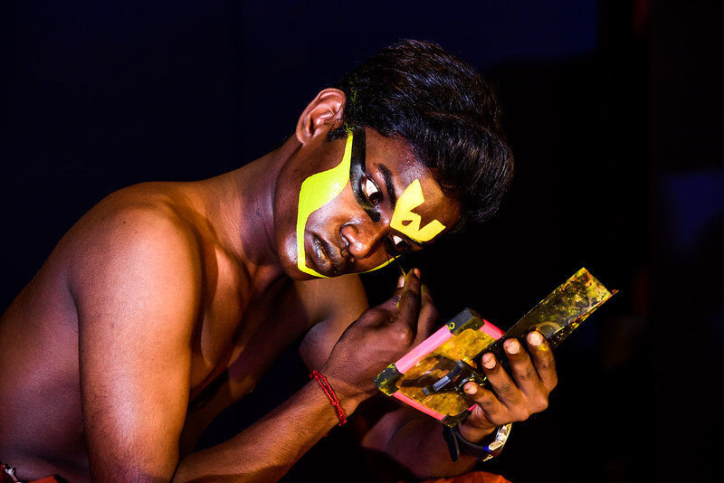 Cochin - A Kathakali dancer putting on his makeup in front of the audience