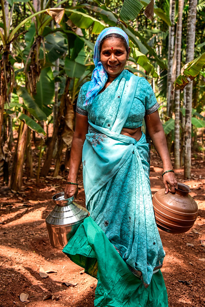 Goa - Plantation worker coming to get water