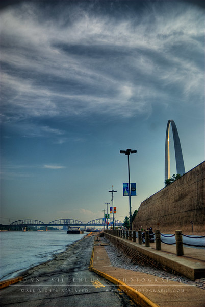 Looking south, the Mississippi River parallels the N Leonor K Sullivan Blvd and Arch. In the distance, you can see the Poplar Bridge and the railroad bridge.