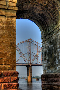 The superstructure of the Martin Luther King Bridge seen through the base of the Eads Bridge.