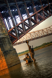 Eads Bridge and the Mississippi River with the Martin Luther King Bridge in the background. In the foreground is a tribute statue of Lewis and Clark.
