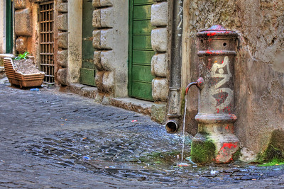A dripping water spigot in Rome, Italy.