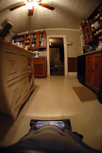 """May 14, 2008; Day 12. I'm hosting a small dinner party tomorrow, so tonight I clean. Oliver suggested that this might be a good time to re-attach the camera to the vacuum. I said I would only if my new 10.5mm Fisheye lens arrived. It did. I think I'm finally happy with my lens collection, which means I can finally put together a """"my gear"""" shot when I have more time.  This is my kitchen, my favorite room in the house. That's a tin ceiling and see-through cabinets. My sister, her husband, and I installed the wallpaper. The camera is taped to a flat section above the main canister of the vacuum. The blur in the photo is due to my actually vacuuming the floor here. A sponge provides vibration dampening, needed since the vacuum is running. Luckily Nikon didn't adopt the term """"vibration dampening"""" for their lenses…"""