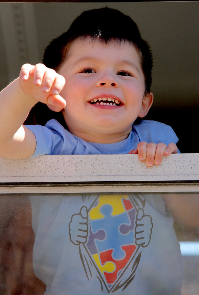 Peabody Mass.  April 23 2017; touch a truck. Bobby Williams (3) waves at his friends from the window of a Peabody Public School bus. BOB ROCHE
