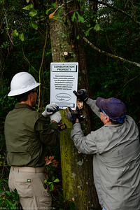 BLC Trail Crew posts a conservation easement sign on the trail.