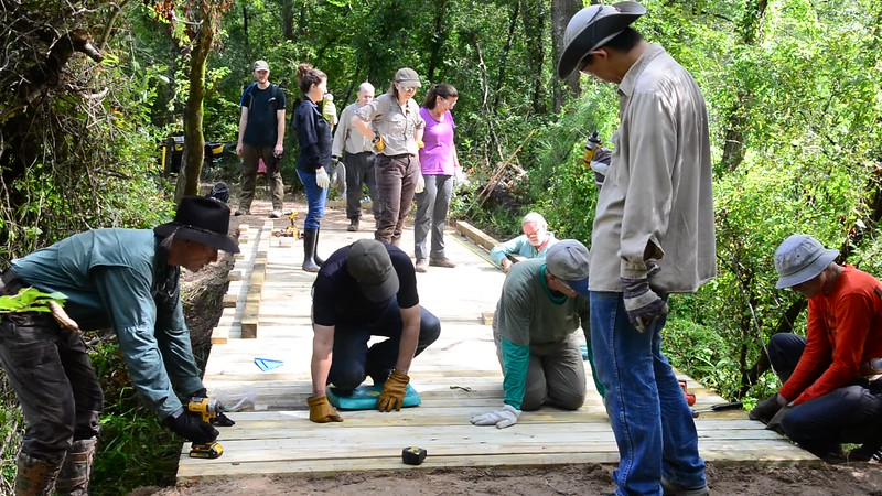 Bayou Land Conservancy Trail Crew volunteers construct the 29 foot long Kahney's Crossing bridge along Spring Creek Nature Trail. This is just 1 of over 20 bridges constucted by the all volunteer crew. bridges constucted by the all volunteer crew.