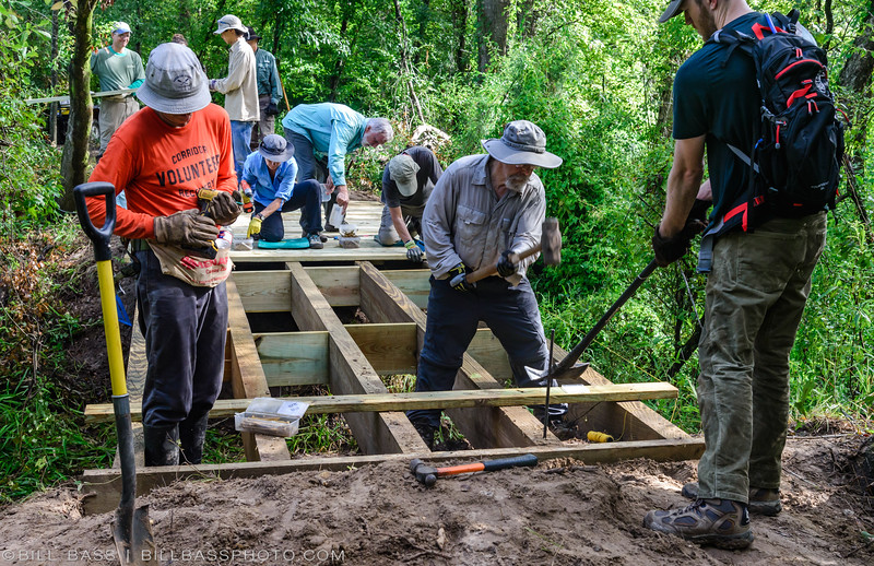 Bayou Land Conservancy Trail Crew volunteers constructing Kahney's Crossing bridge on the Spring Creek Nature Trail near The Woodlands, Texas. At 29 feet long it is one of the largest bridges constructed along the trail.