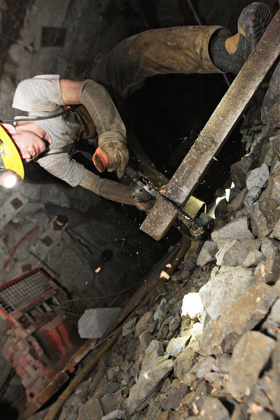Miner Brandon Favar cuts a stull to reinforce a tunnel wall at the 2400 foot level at the Galena Mine, in Wallace, Idaho on Wednesday January 4, 2012. A stull is a piece of timber that is placed diagonally in a tunnel for support.  (Young Kwak Special to the Pacific Northwest Inlander)