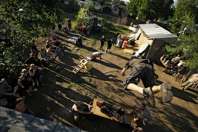 """Steven """"Killer"""" Jenkins jumps off the roof of a house onto Zach """"Komodo"""" Pabst during the 6 Man Iron Match, a part of Spokane Anarchy Wrestling's Wrestle Rave 4 at a private residence in Spokane, Wash. on Saturday, June 26, 2010. (Young Kwak Special to the Pacific Northwest Inlander)"""