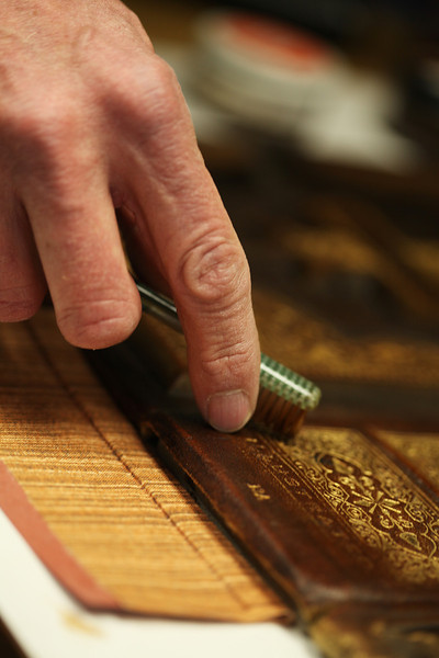 Owner Willem Bosch demonstrates how he uses a toothbrush to remove excess shoe polish during the restoration process of an old family Bible, at Arts & Crafts Book Manufacturing Co., in Spokane, Wash., on Thursday, April 26, 2012. (Young Kwak/The Pacific Northwest Inlander)