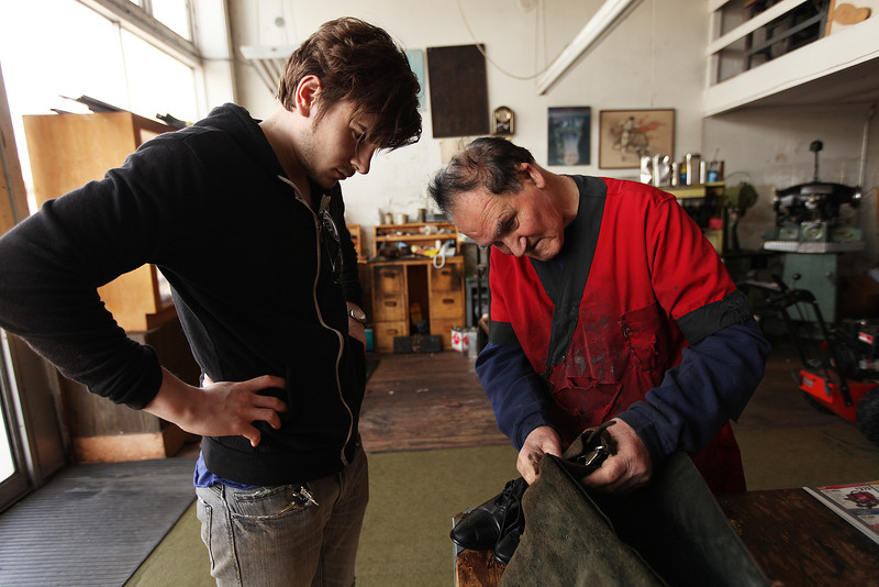 Owner Cruz Albisu, right, speaks with customer Nikolai Cherny on repairs that were made to shoes and a bag at Cruz Custom Boots & Shoes, in Spokane, Wash., on Wednesday, April 25, 2012. (Young Kwak/The Pacific Northwest Inlander)