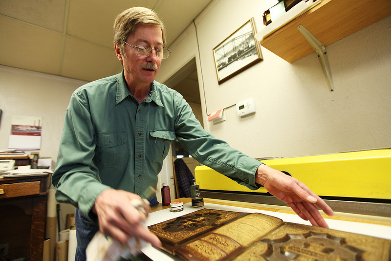 Owner Willem Bosch moves the cover of an old family Bible during a demonstration of the restoration process, at Arts & Crafts Book Manufacturing Co., in Spokane, Wash., on Thursday, April 26, 2012. (Young Kwak/The Pacific Northwest Inlander)