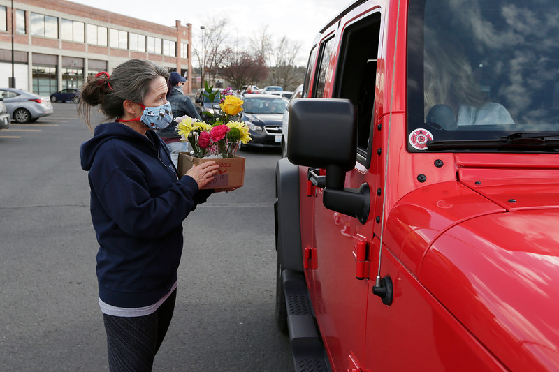 "Volunteer Keirsten Lyons hands flowers donated by Rosauers Supermarkets at 5-mile and the ""Y"" to volunteer Jerrie Allard to deliver to with meals during a Spokane Food Fighters distribution of meals for volunteers to deliver to people who have made emergency meal requests to the organization, at Riverwalk in Spokane, Wash., Monday, April 6, 2020. (Young Kwak/The Inlander)<br /> <br /> Photo for story about Spokane Food Fighters delivering meals during the COVID-19 pandemic."
