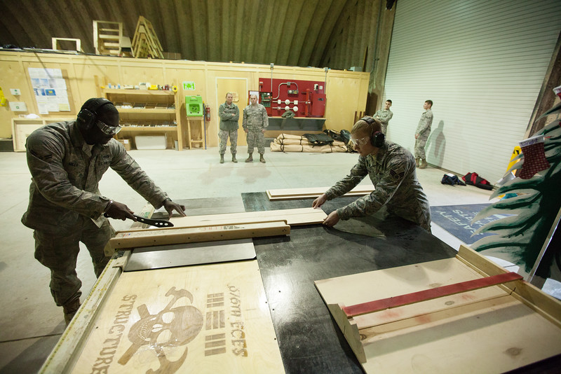 376th Expeditionary Civil Engineers Airman Fist Class Michael Mills, left, and Senior Airman Andrew Camerly demonstrate how to rip wood, at the Transit Center at Manas, Kyrgyzstan, on Friday, Dec. 13, 2013. These members of the expeditionary unit's home unit is the 92nd Civil Engineers at Fairchild Air Force Base, Wash. (Young Kwak/The Pacific Northwest Inlander)