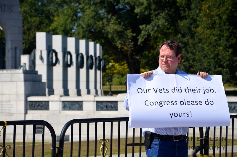 A man protests the federal government shutdown by the World War II Memorial.