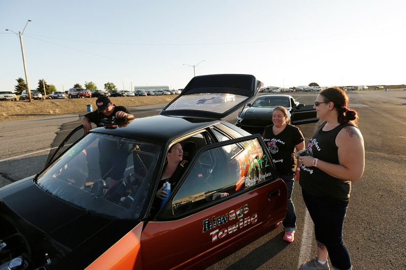 Miss Shifters members Heather Eller, right, and Shelly Walsh, second from the right, speak with President Rachelle Stephens, second from the left, who is sitting in her 1984 Ford Mustang GT, as Stephens' husband Casey Stephens looks on, during the Summit #6 Sugar Bear Memorial at the Spokane County Raceway in Airway Heights, Wash., Saturday, July 14, 2018. (Young Kwak/The Inlander)