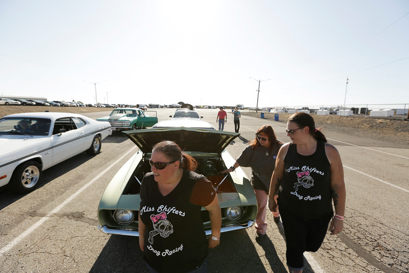 Miss Shifters members Shelly Walsh, left, and Heather Eller, right, walk with Treasurer Annette Callesto next to Callesto's 1969 Chevrolet Camaro before a Powder Puff time trial, during the Summit #6 Sugar Bear Memorial at the Spokane County Raceway in Airway Heights, Wash., Saturday, July 14, 2018. (Young Kwak/The Inlander)