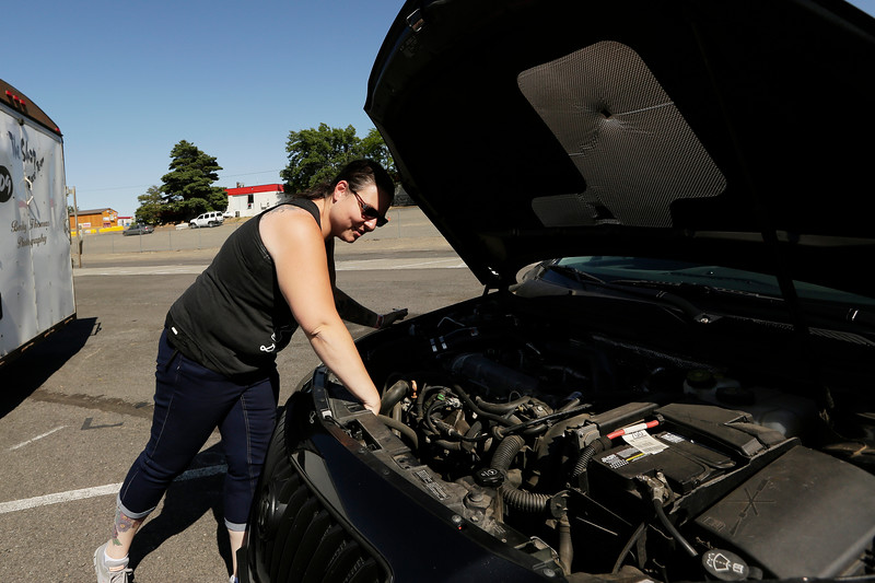 Miss Shifters member Heather Eller checks the temperature on her 2011 Buick Regal Turbo before racing, during the Summit #6 Sugar Bear Memorial at the Spokane County Raceway in Airway Heights, Wash., Saturday, July 14, 2018. (Young Kwak/The Inlander)