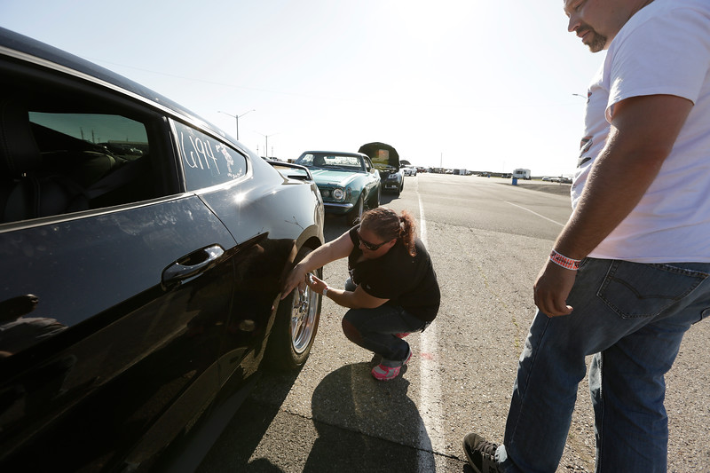 Miss Shifters member Shelly Walsh,, left, checks the tire pressure on her 2018 Ford Mustang GT before a Powder Puff time trial, while speaking with Kris Page, during the Summit #6 Sugar Bear Memorial at the Spokane County Raceway in Airway Heights, Wash., Saturday, July 14, 2018. (Young Kwak/The Inlander)