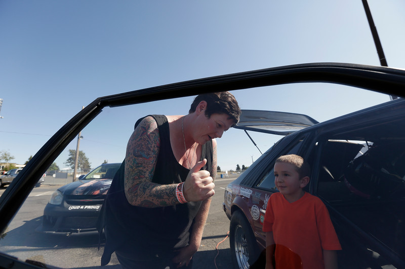 Miss Shifters President Rachelle Stephens, left, discusses  her 1984 Ford Mustang GT with 6 year old Jacen Lake, during the Summit #6 Sugar Bear Memorial at the Spokane County Raceway in Airway Heights, Wash., Saturday, July 14, 2018. (Young Kwak/The Inlander)