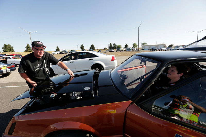 Miss Shifters President Rachelle Stephens, right, looks on as her husband Casey Stephens places the hood on her 1984 Ford Mustang GT before a Powder Puff time trial, during the Summit #6 Sugar Bear Memorial at the Spokane County Raceway in Airway Heights, Wash., Saturday, July 14, 2018. (Young Kwak/The Inlander)