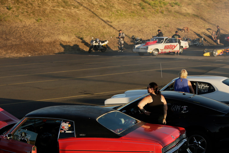 Miss Shifters member Heather Eller, bottom, stands next to her 2011 Buick Regal Turbo before the second Powder Puff elimination round, during the Summit #6 Sugar Bear Memorial at the Spokane County Raceway in Airway Heights, Wash., Saturday, July 14, 2018. (Young Kwak/The Inlander)