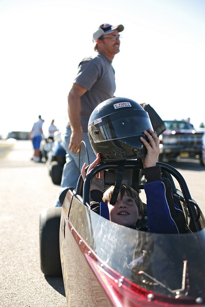 13 year old Junior Dragster Class Driver Jake Nickerson, right, puts on his helmt as his father walks by at the Spokane County Raceway drag strip, in Airway Heights, Wash., on Saturday, August 25, 2012. The Nickerson family lives in Spokane Valley, Wash. Each member of the family races drag cars, including mother Merri, 22 year old brother Cody and 18 year old brother Dylan. (Young Kwak/The Pacific Northwest Inlander)