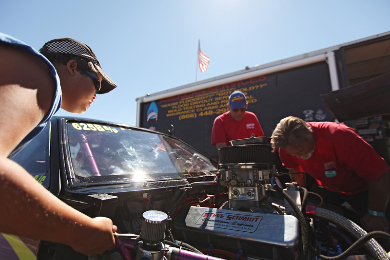(Left to right) 16 year old Devin Clark changes the rag on a puke tank as Mike Streeter and Owner/Driver Brooks Swanson work his Super Pro Class 1978 Manza chassis Chevy 555 V8 before a race at the Spokane County Raceway drag strip, in Airway Heights, Wash., on Saturday, August 25, 2012. Swanson and Streeter are from Priest River, Idaho while Clark is from Spokane, Wash. The puke tank holds dirty oil from the motor. (Young Kwak/The Pacific Northwest Inlander)
