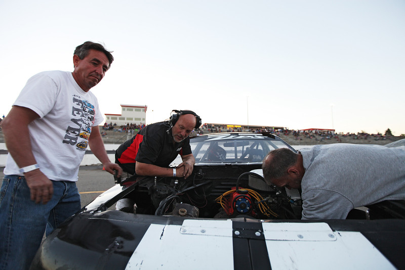 Bill Husk, right, fixes a stripped motor mount bolt on Pit Director and Vehicle Owner Corky Harbison's, center, car, as Rich Hatton looks on, at the Spokane County Raceway oval racetrack, in Airway Heights, Wash., on Friday, August 24, 2012. (Young Kwak/The Pacific Northwest Inlander)