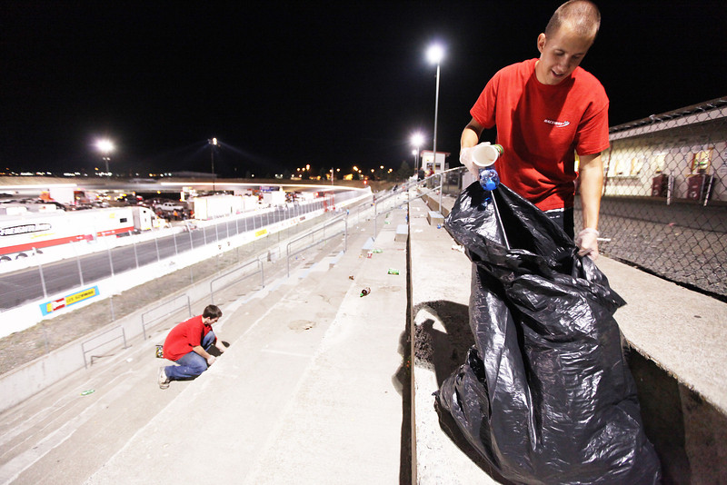 Employees Ian Kuula, right, and Cole Hobert-Swanson pick up trash after the Spokane 200, at the Spokane County Raceway oval track, in Airway Heights, Wash., on Saturday, August 25, 2012. (Young Kwak/The Pacific Northwest Inlander)