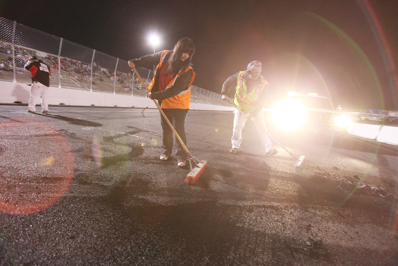 Fire crew members 15 year old Megan McCormick, left, and her father David Childs sweep tire rubber off the oval racetrack after Bump To Pass Driver Justin Kirk did a burnout after a race at at the Spokane County Raceway, in Airway Heights, Wash., on Friday, August 24, 2012. (Young Kwak/The Pacific Northwest Inlander)