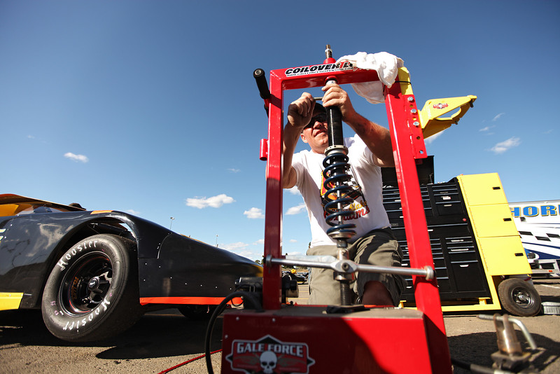 Crew Chief Kevin Richards installs a new spring on a shock for 17 year old West Valley High School Junior Blake Williams', not pictured, Late Model Class car  at the Spokane County Raceway oval racetrack, in Airway Heights, Wash., on Friday, August 24, 2012. The vehicle runs Victory Circle chassis with a Ford V8 engine. (Young Kwak/The Pacific Northwest Inlander)