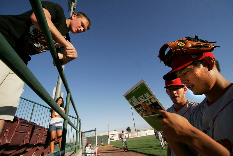 Spokane Indians second baseman Jason Ogata, right, and short stop Edward Koncel sign autographs for 14 year old Ryan Wingate, left, as 12 year old Rachel Wingate looks on at Gesa Stadium, in Pasco, Wash., Monday, August 4, 2008. The two Wingate children are in Richland, Wash., visiting relatives and are from Greentown, Ind.  The Spokane Indians beat the Tri-City Dust Devils 13-9 that evening in a Northwest League game (Young Kwak Special to the Pacific Northwest Inlander)