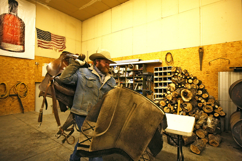 Nate Gutzweiller brings saddles out at Lazy H Ranches, in Cheney, Wash., on Monday, November 7, 2011. (Young Kwak Special to the Pacific Northwest Inlander)