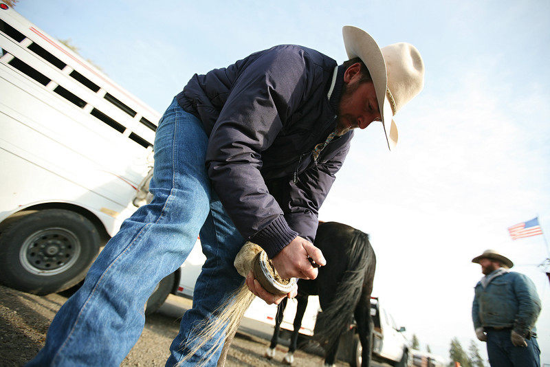 Cody Dix Harris cleans his horse's shoe at Lazy H Ranches, in Cheney, Wash., on Monday, November 7, 2011. (Young Kwak Special to the Pacific Northwest Inlander)