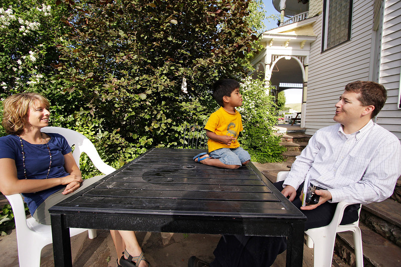 Kelly, left, and Tony Lundgren, DO, speak as their 3 year old son Marcos plays at their house in St. John, Wash. on Tuesday, June 29, 2010. Marcos, from Guatemala, is the adopted son of Kelly and Tony Lundberg, DO. Marcos is one of 5 children adopted by the Lundbergs. Tony Lundberg serves as the town's physician. Tony grew up in Las Vegas, went to school at Kirksville College of Ostheopathics in Missouri. He did his residency in Colville, Wash. as part of a University of Washington program and moved to St. John after his residency to become the town physician. He and Kelly met at BYU, where they were married between their Junior and Senior years. The house is known as the Doctor's House, which was built to house the town physician. (Young Kwak Special to the Pacific Northwest Inlander)