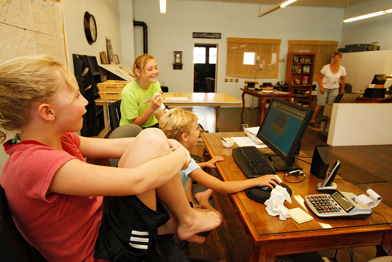 9 year old Glory Dickerson, left, and 10 year old Carmen Gfeller, right, watch 7 year old Roxy Dickerson play an online video game at the Community Current newspaper office in St. John, Wash. on Tuesday, July 6, 2010. In the background is Becky Dickerson, who is publisher and editor of the newspaper. The children often play at the newspaper office. Dickerson started the newspaper 15 years ago and publishes monthly. (Young Kwak Special to the Pacific Northwest Inlander)