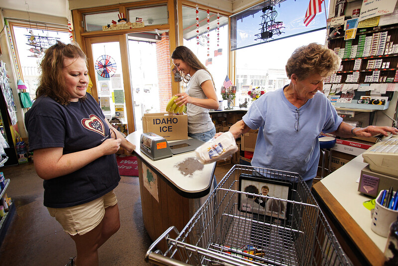 Owner Marilyn Webb, right, and her 18 year old granddaughter Kelly Van-Lith, center, help customer Monica Jones at St. John Empire Foods in St. John, Wash. on Tuesday, June 29, 2010. The Webb family has been in the St. John area since 1905. The store has been in business since 1968 and remains as the only grocery store in town. Kelly is an incoming freshman at Gonzaga University in Spokane, Wash. She is working for the first time at the store during the summer. (Young Kwak Special to the Pacific Northwest Inlander)