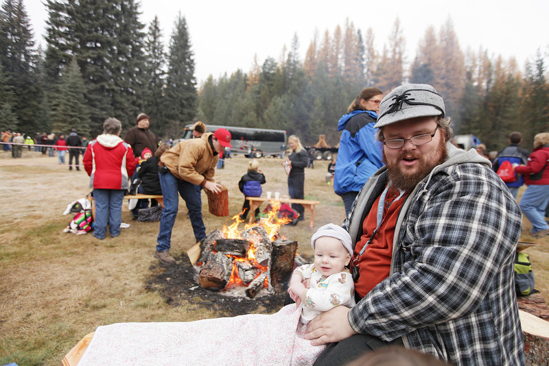 Goff Daily, right, holds his 9 month old son Sean before an eighty-eight foot Engelmann Spruce, destined to be the U.S. Capitol Christmas Tree, is cut, in the Colville National Forest, in Pend Oreille County, Wash., on Friday, November 1, 2013. (Young Kwak/The Pacific Northwest Inlander)
