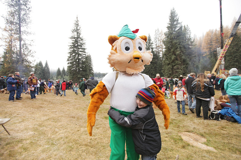 6 year old Riley Sampson hugs Woodsy Owl before an eighty-eight foot Engelmann Spruce, destined to be the U.S. Capitol Christmas Tree, is cut, in the Colville National Forest, in Pend Oreille County, Wash., on Friday, November 1, 2013. (Young Kwak/The Pacific Northwest Inlander)