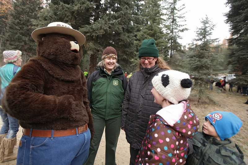 Smokey the Bear, left, hangs out with (left to right) U.S. Forest Service employee Gayne Sears, Chelsea Earls, her 8 year old daughter Olivia and 5 year old son Oliver before an eighty-eight foot Engelmann Spruce, destined to be the U.S. Capitol Christmas Tree, is cut, in the Colville National Forest, in Pend Oreille County, Wash., on Friday, November 1, 2013. (Young Kwak/The Pacific Northwest Inlander)