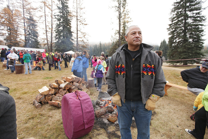 Kalispel Tribe Cultural Program Assistant Director J.R. Bluff keeps a drum warm before an eighty-eight foot Engelmann Spruce, destined to be the U.S. Capitol Christmas Tree, is cut, in the Colville National Forest, in Pend Oreille County, Wash., on Friday, November 1, 2013. (Young Kwak/The Pacific Northwest Inlander)