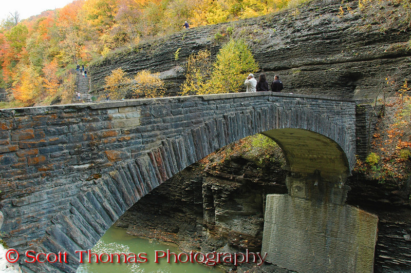 "This stone footbridge was built in 1935 below the Lower Falls giving views of those falls and the gorge area.  The previous photo of the Lower Falls was taken from here.  The bridge spans 46 feet and is 35 feet above the Genesee River.  It is the only pedestrian crossing of the river in Letchworth State Park. (reference <a href=""http://www.waymarking.com/waymarks/WM2YZX"" target=""new"">Waymarking.com</a>)  Bring waterproof footwear with you if you hike down <a href=""http://www.waymarking.com/waymarks/WM3BF5"" target=""new"">from the Parade Grounds</a>.  The platform above, stairs to get to here and bridge are muddy and extremely slippery."