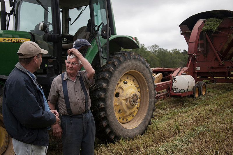 """Bob takes a break from work to speak to his son, Roger. Bob Nutter is the owner of Maple View Farm, Inc. Now 85 years old, Bob is semi-retired. But due to his long life committed to farming as well as his passion for it, you can find Bob on his tractor any day of the week and """"retired"""" isn't often used in reference to him. He is also the errand runner and tour guide at the Agriculture Center. Bob is working toward handing over full ownership of the herd to Mike Strowd who took over active management of the farm in 2008. Maple View hopes by handing over the farm to Mike, the future of the farm will look bright."""