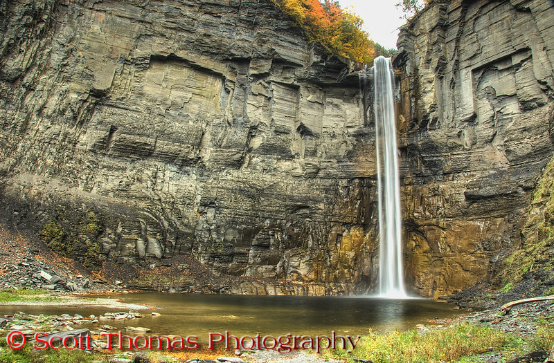 "<a href=""http://www.priweb.org/ed/finger_lakes/taughannock_falls.html"" target=""new"">Taughannock Falls</a> as seen from the viewing area is 215 feet high which is 33 feet higher than Niagara Falls. It is the highest free-falling waterfall in the northeastern United States, and one of the highest waterfalls of any kind east of the Rocky Mountains. The water hits with such force, the plunge pool at the bottom is 30 feet deep.  The gorge walls are made up of soft shale which has allowed the Taughannock Creek to cut a wide, flat delta unlike the other gorges in the area.  The morning I took this was very cold, drizzly and cloudy.  Using a tripod, a polarizer filter and bracketed long exposures off a tripod. I used Photomatix software to create this HDR image. HDR brought out all the detail of the gorge walls and plunge pool while the polarizer filter cut out all the glare off the water's surface."
