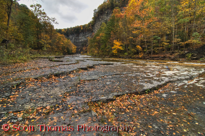 The gorge trail to the <b>Taughannock Falls</b> viewing area is 3/4 of a mile long and fairly flat and accessible.  The trail follows the south gorge wall with the Taughannock Creek just to the north.    During late Fall, the creek is low and stays confined to the deepest flow areas.  In this photo, you can see the exposed creek bed at low flow.  In the Spring and after heavy rainfalls, these are submerged.  The High Dynamic Range, or HDR, let me capture the bright sky, shadowed cliff walls and details in the exposed creek bed.  If I had taken this without the sky, I think it would not have had the same impact.